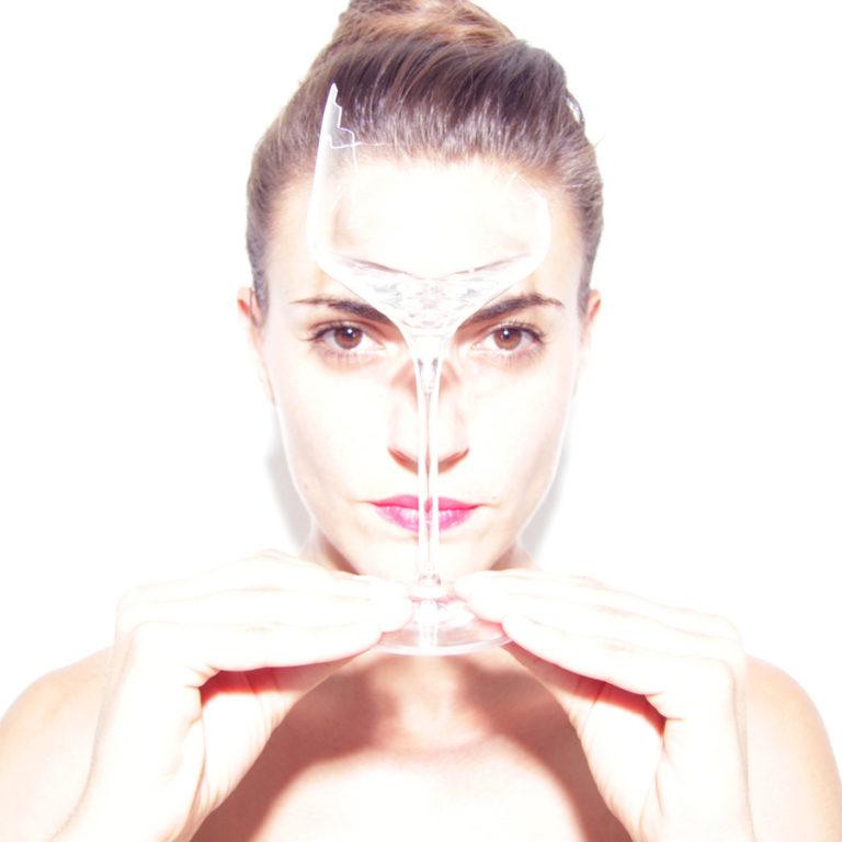 Photographie d'une femme tenant un verre cassé devant son visage